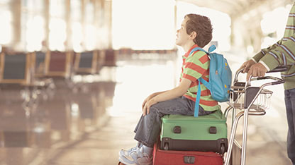 Boy sitting on suitcase at airport