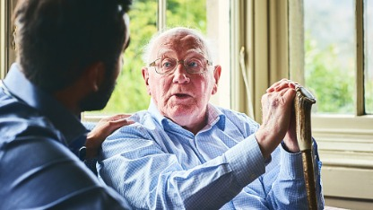 Elderly man talking with carer