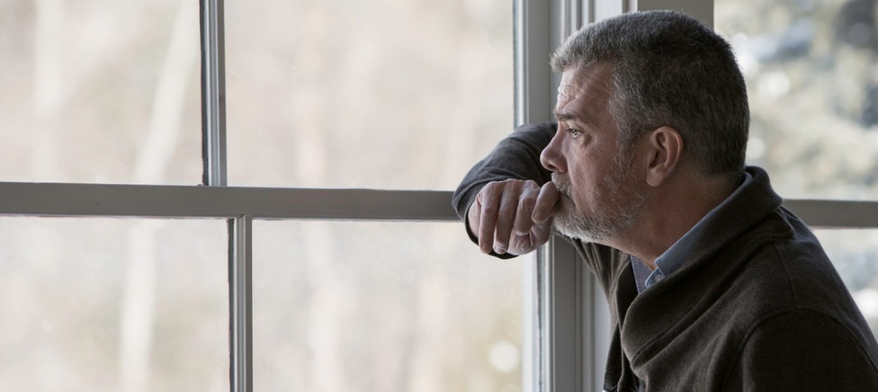 Grieving man at window